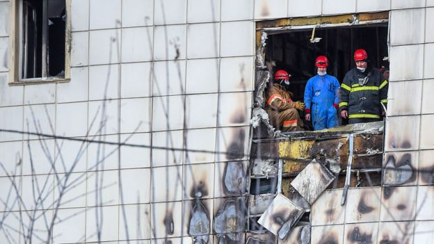 Russian emergency service staff work at the site of a fire at a multi-storey shopping centre in Kemerovo on March 27, 2018