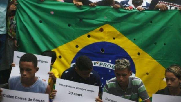 Bandeira do Brasil com buracos para representar tiros de 111 balas disparadas contra 5 jovens no Rio, em 2015