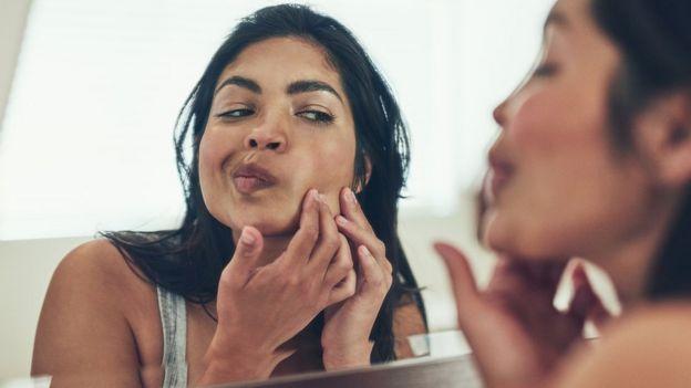 Девушка разглядывает кожу в зеркало