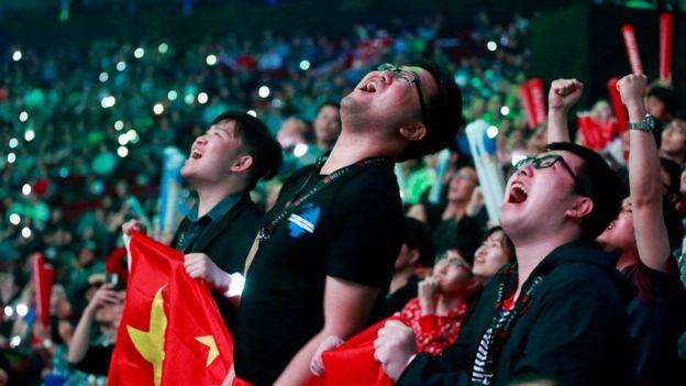 Os fãs de jogos do PSG.LGD reagem durante a grande final do Dota 2 entre PSG.LGD e OG no Dia 6 do The International 2018 na Rogers Arena em 25 de agosto de 2018 em Vancouver, Canadá
