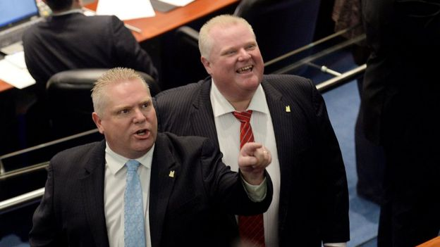 Doug Ford (L) reacts to someone in the city council chambers while Rob Ford looks on