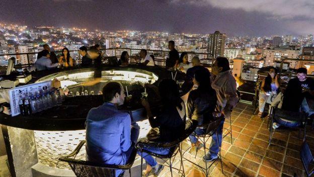 En la terraza del 360 algunos venezolanos pueden disfrutar de un cóctel y de las vistas panorámicas de Caracas. Foto: AFP