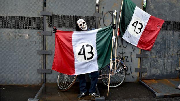 """Una persona enmascarada sosteniendo dos banderas de México en las que se lee """"43""""."""