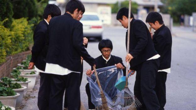 Estudiantes limpiando.