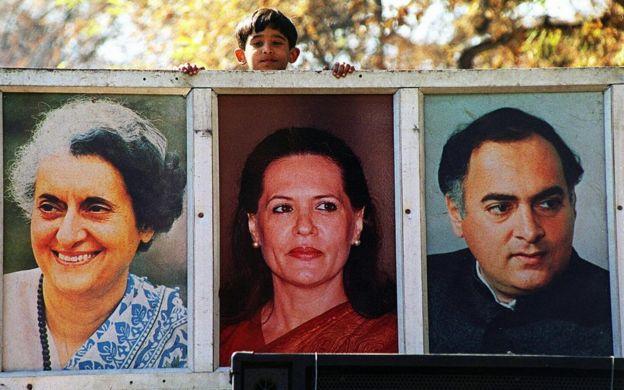 Молодой мальчик сверкает с вершины рекламного грузовика партии Конгресса, где представлены увеличенные фотографии (LR) Индира Ганди, Соня Ганди и Раджив Ганди.