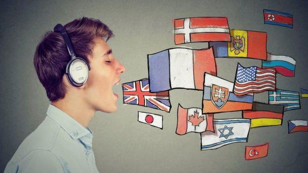 Imagem mostra jovem com fones de ouvidos, próximo a bandeiras de vários países, para simular que está falando vários idiomas