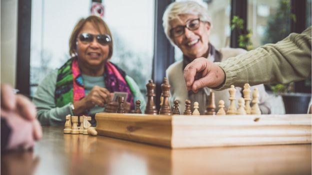 idosas olham uma pessoa jogando xadrez