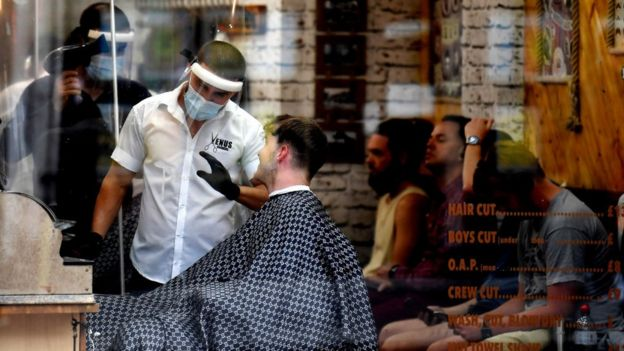 Barbers in masks serve customers as many others wait their turn in Clapham