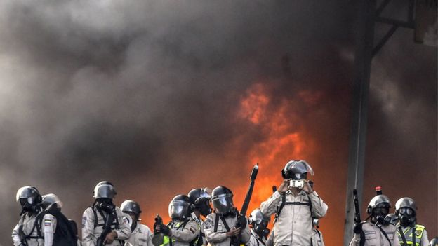 Manifestantes com mascaras e fogo nas ruas durante protestos na Venezuela
