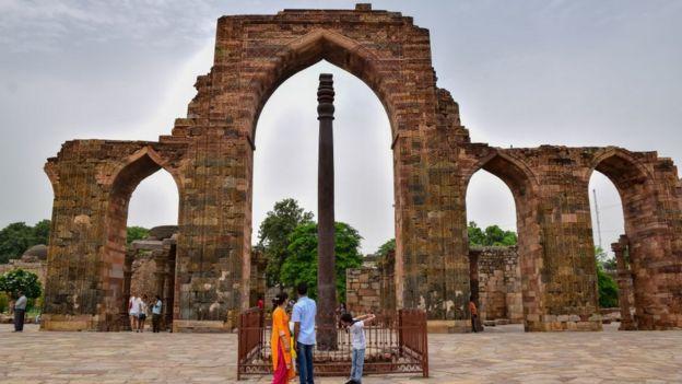 Pessoas observam o Pilar de Ferro de Déli, na Índia