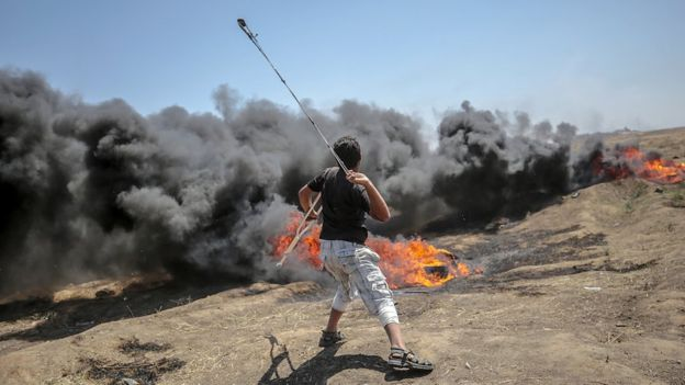 A Palestinian protester throws stones during clashes after protests near the border with Israel in the east of Gaza Strip, 14 May 2018 (