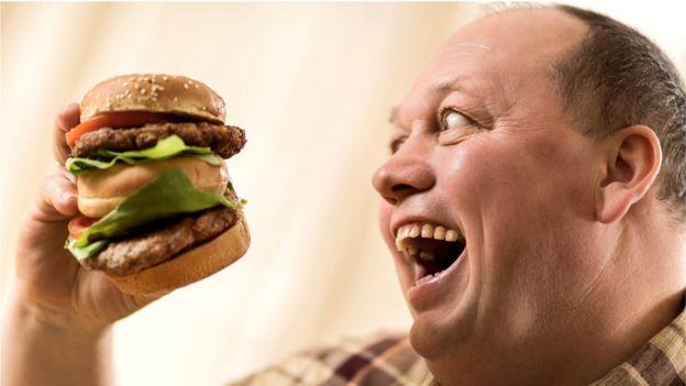 homem comendo burger