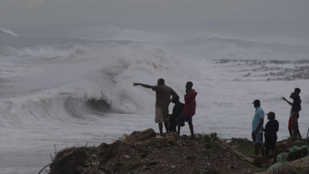 People stand on the coast watching the surf produced by Hurricane Matthew, on the outskirts of Kingston, Jamaica