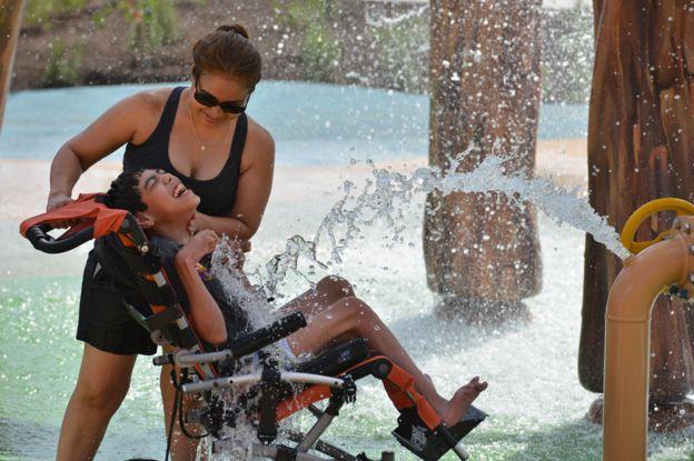 Um menino com a mãe no parque aquático