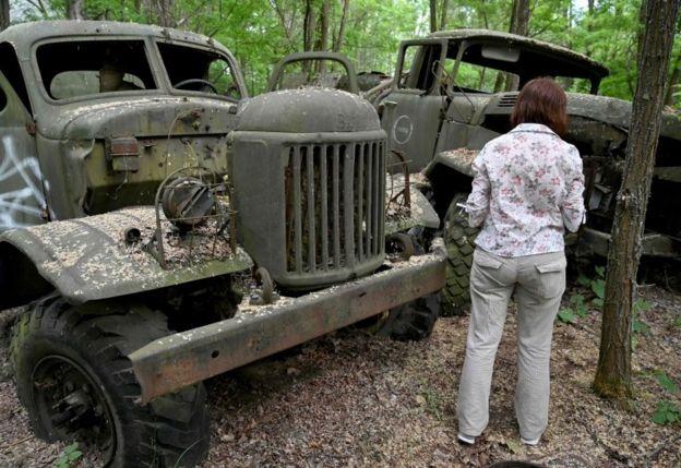 Una mujer frente a viejos y abandonados vehículos en una excursión turística en la ciudad abandonada de Prípiat.