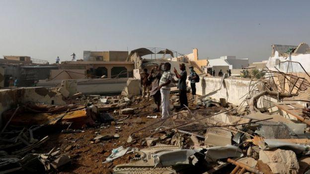 علاقے کے افراد ایک گھر کی چھت پر کھڑِے ہوئے ہیں جس پر ملبہ دیکھا جا سکتا ہے