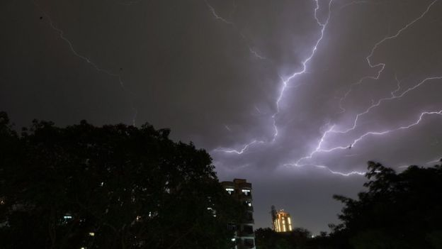 Lightning strikes over residential apartments during a thunderstorm on the outskirts of the Indian capital Delhi on 2 May 2018