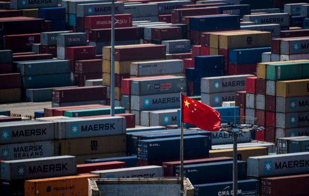 Bandeira chinesa em meio a containeres em porto