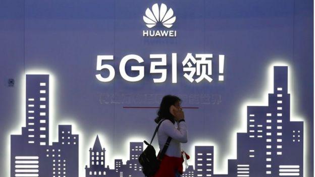 Una mujer camina frente a un póster de Huawei en Pekín, China.