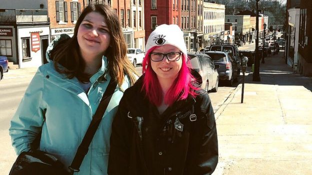 Two girls smiling at the camera. Behind them is a metropolitan street.