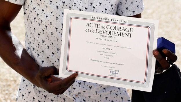 Mamoudou Gassama holds a certificate he was given for climbing up a building to rescue a boy