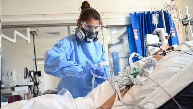 Médica de equipamento de proteção trata de paciente em hospital