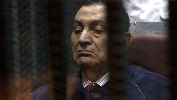 Mubarak muncul di balik jeruji besi dalam pengadilan tahun 2014.