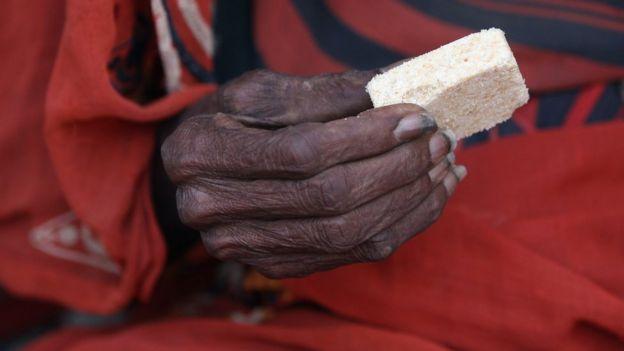Кусок пищи в руке пожилой женщины