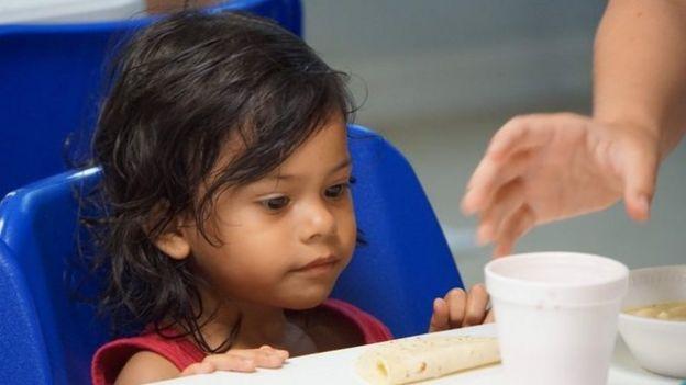 Menina sentada se prepara para comer em centro de detenção de imigrantes na cidade fronteiriça de McAllen, no Texas (EUA):