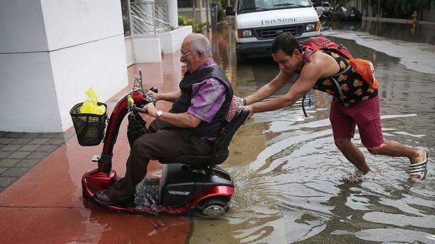 Un joven empuja la silla de ruedas eléctrica de un hombre mayor.