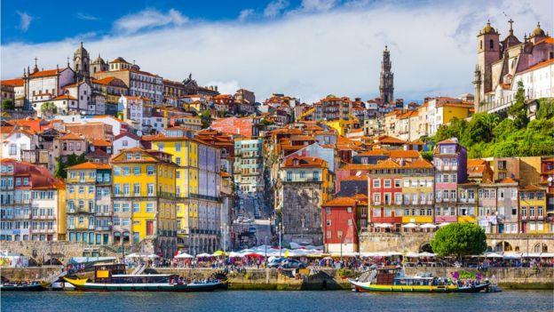 Imagem mostra imóveis e barcos na cidade do Porto, em Portugal