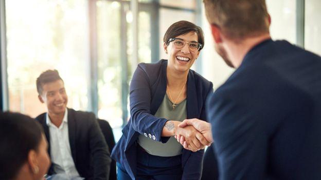 Una mujer le da la mano a un hombre durante una reunión empresarial
