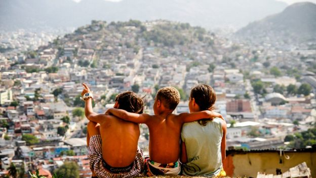 Tres niños en la cima de una favela contemplando la vista.