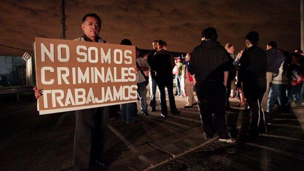 """Un hombre sostiene un cartel que dice """"No somos criminales, trabajamos"""""""