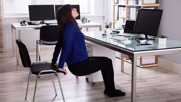 Mujer estirándose en la oficina