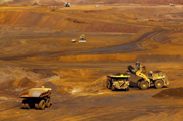 Workers stand around a vehicle as a truck is loaded with iron ore at the Fortescue Metals Group