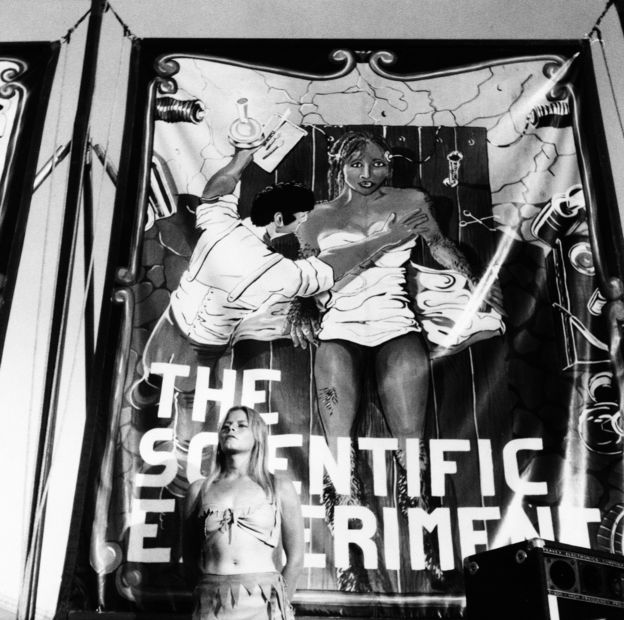 Mulher em frente ao cartaz do show de mulher-gorila