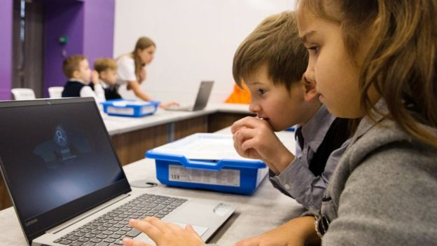 Niños en clase con una computadora.