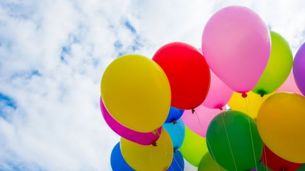 Colourful helium balloons over a cloudy sky