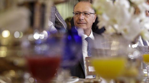 Alckmin sentado em mesa de evento