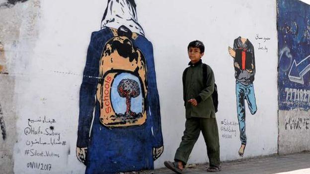 تحكي الجدارية قصة طفل بترت ساقه بسبب الألغام يقدم ساقه هدية للعالم الذي لا يكترث، وطالبة ترتدي الزي المدرسي وحقيبتها المدرسية مرسوم عليها صورة تفجير، كما قالت الرسامة اليمنية