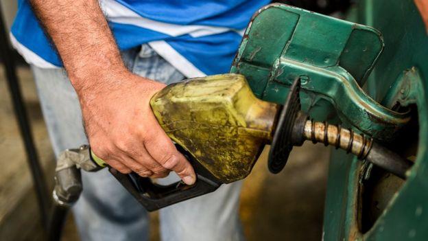Hombre llenando tanque de gasolina.