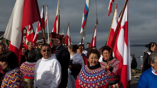 People standing, Greenlandic and Danish flags