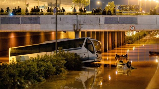 People look on a bus and cars submerged in a flooded road, in Mandra, near Athens