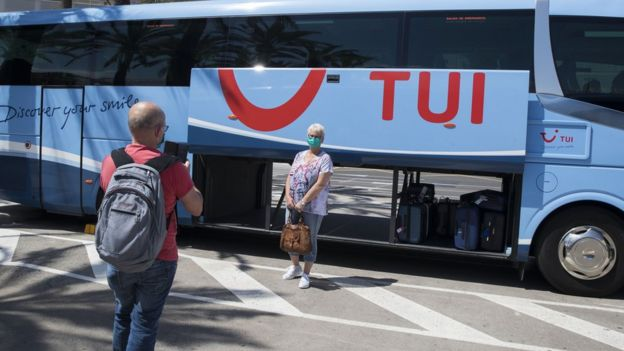 A masked Tui customer poses beside one of the firm's coaches in Spain