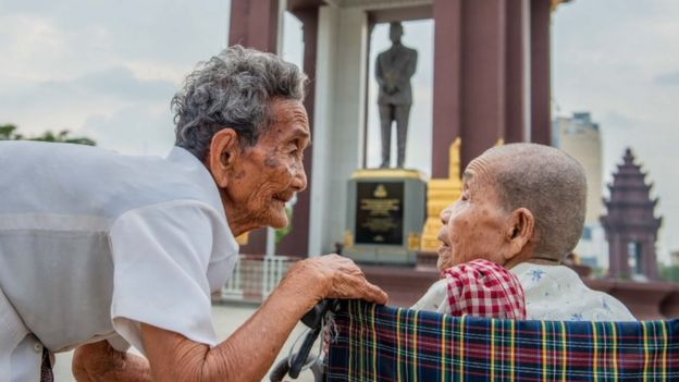 Bun Sen agacha-se perto de Bun Chea, que está em uma cadeira de rodas; ambas aparecem em frente a estátua de figura histórica na capital cambojana, Phnom Penh