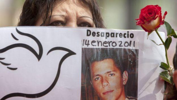 Madre de un desaparecido con la foto de su hijo desaparecido el 14 de enero de 2011