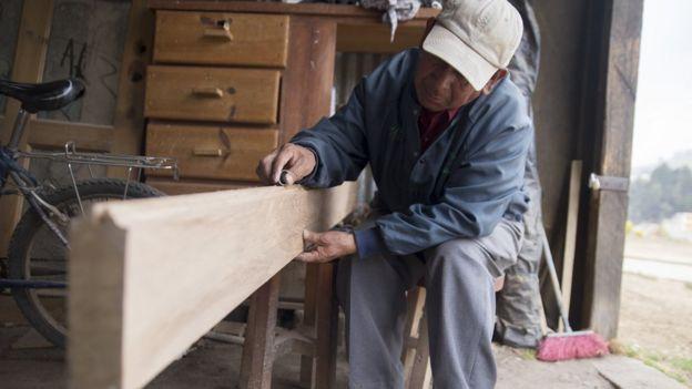 A man works in a carpentry workshop in Zunil