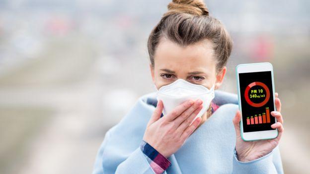 Mujere con una máscara y un celular que muestra el nivel de partículas gruesas de contaminación o PM10.