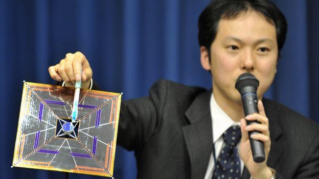 El científico Yuichi Tsuda sosteniendo un modelo del satélite IKAROS en una conferencia.